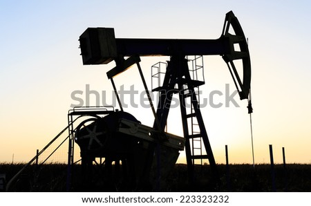 Oil and gas well silhouette in remote rural area, profiled on sunset sky