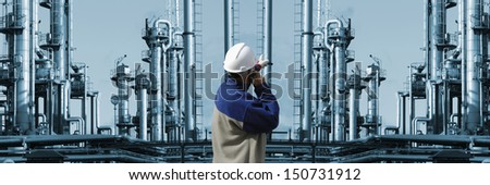 oil and gas worker pointing at large industrial refinery installation - stock photo