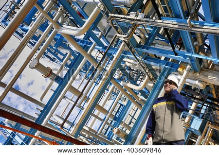 oil and gas worker with pipelines construction in background - stock photo