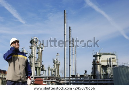 oil and gas worker with refinery in background - stock photo