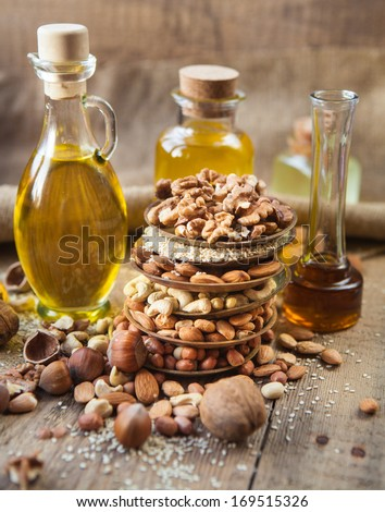 oil and mixed nuts on a rustic background - stock photo