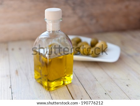 oil bottle isolated on rustic wooden background - stock photo