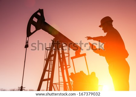 Oil Drill, field pump jack silhouette with setting sun and worker. Lens Flare. See more images and video from this series and Refinery series.  - stock photo