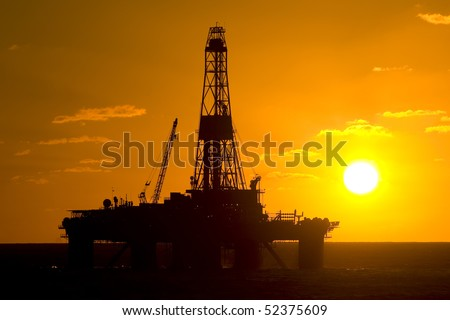 oil drilling rig in offshore area during sunset time - stock photo