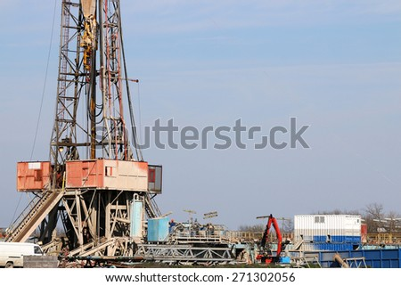 oil drilling rig with equipment on oilfield - stock photo
