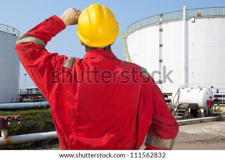 Oil engineer looking at overdue maintenance and safety issues of storage tanks with crude oil supply - stock photo