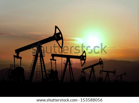oil field and pump jack on sunset - stock photo