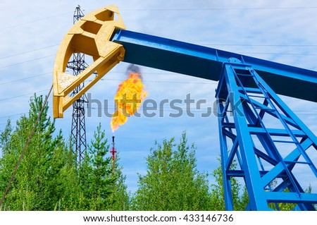 Oil field. Oil rocking a torch gas with the background. - stock photo
