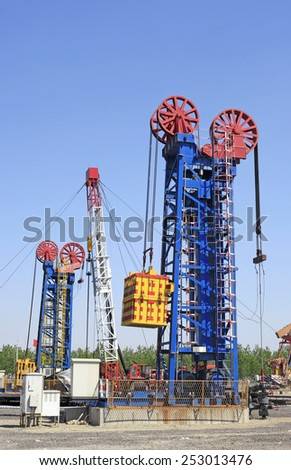 Oil field scene, beam pumping unit and tower type pumping unit in the work - stock photo