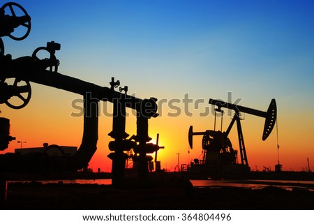 Oil field scene, Oil pipeline and pumping unit of the silhouette - stock photo