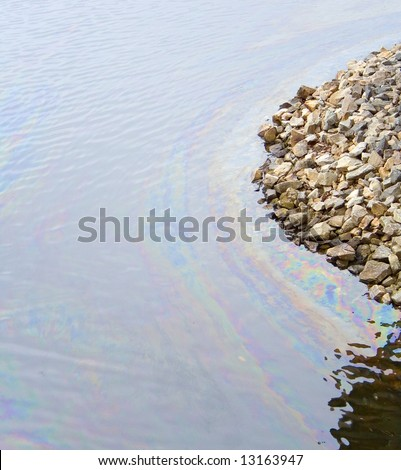 oil film pollution on top of water damage to environment sea stone bank - stock photo