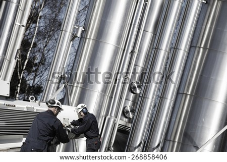 oil, fuel and gas workers with giant gas-pipes machinery - stock photo