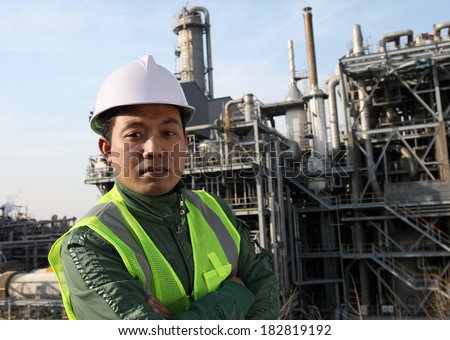 Oil gas engineer wearing safety work standing front of large oil industry