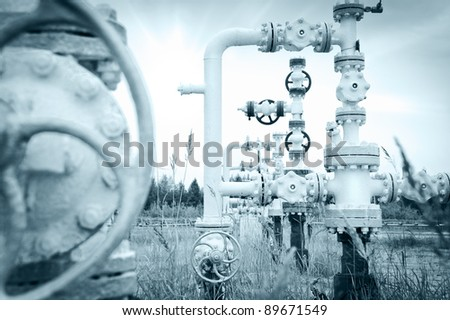 Oil, gas industry. Group wellheads and valve armature on a sky background. Toned. - stock photo