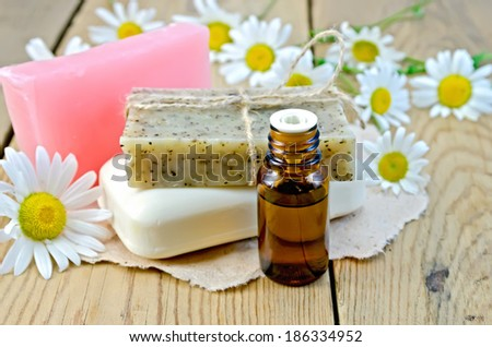 Oil in a bottle, homemade soap on a piece of paper, daisy flowers on a background of wooden boards - stock photo