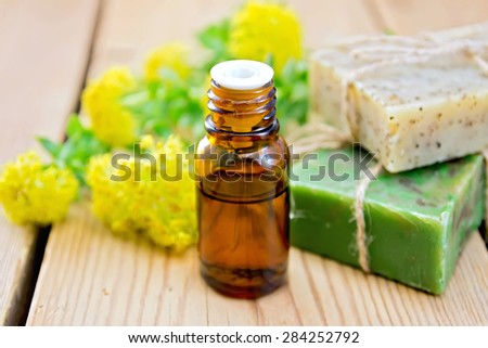 Oil in a bottle, two bars of homemade soap, flowers and leaves of Rhodiola rosea on a wooden boards background - stock photo