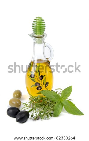 oil in bottle and herbs on white background