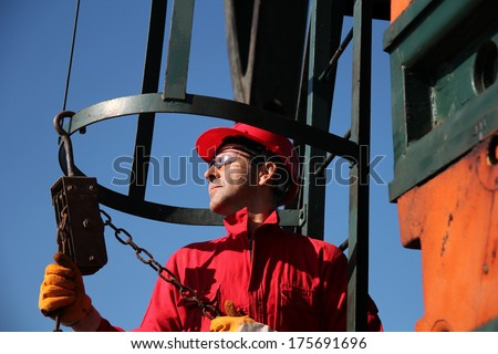 Oil Industry Worker Using Chain Winch.Oil industry worker in action with chain winch at pump jack oil well - stock photo