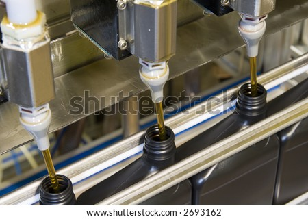 Oil is dispensed into quart bottles at a lubricant manufacturing facility - stock photo