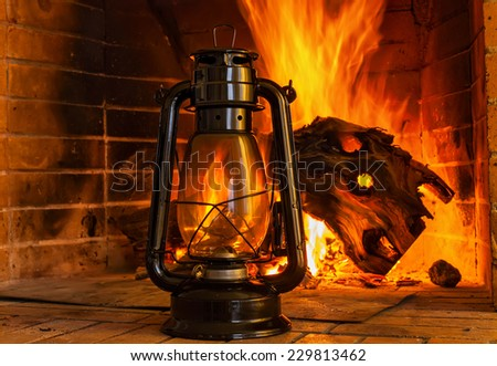 Oil lamp near the fireplace on a background of fire - stock photo