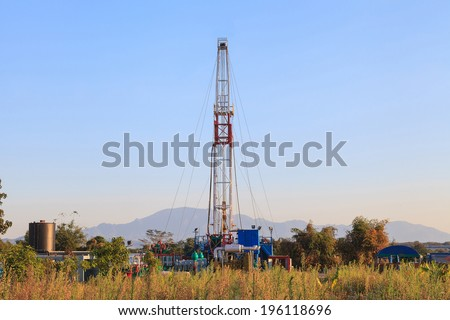 Oil Land Drilling Rig Working In The Field For Petroleum Exporation at Sunset Time - stock photo