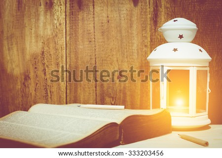 oil lantern lamp burning with a soft glow light & pencil on book, old aged wood background