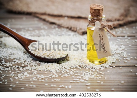 Oil of sesame seeds in a bottle with a sign . The rustic style. Shallow DOF - stock photo