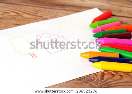 Oil pastel crayons lying on a paper with painted children's drawing. Copy space background. Selective focus - stock photo
