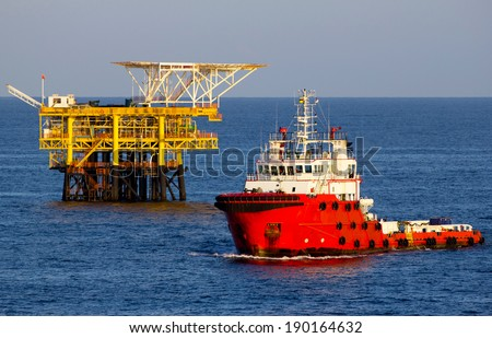 Oil platform and a supply vessel at sunset - stock photo