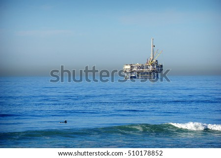 oil platform and surfers in pacific ocean