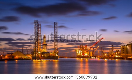 Oil Platforms being built in a manufacturing harbor under beautiful sunset - stock photo