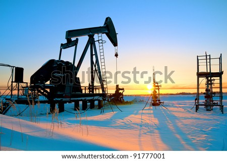 Oil pump against the rising sun - stock photo