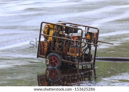 Oil pump evacuate crude oil spilled on the beach in Thailand. - stock photo
