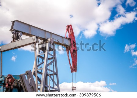 Oil pump in the open air, on a background of the cloudy sky
