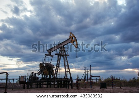 Oil pump jack and wellhead with valve armature during sunset on the oilfield. Extraction of oil. Oil and gas concept. Dramatic cloudy sky background.