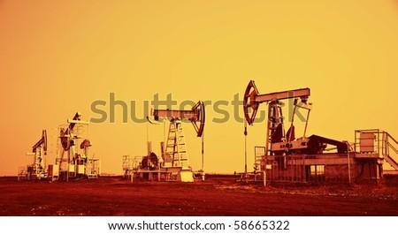 Oil pump jack.Orange filtered image. - stock photo