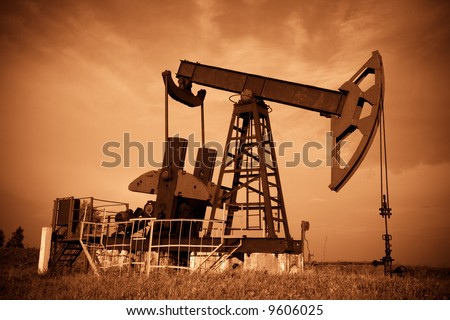 Oil pump jack. Red filtered image. - stock photo