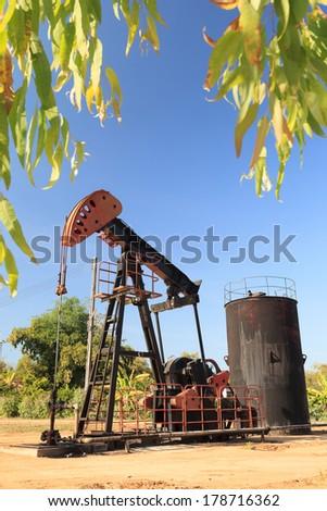 Oil Pump Jack (Sucker Rod Beam) on Sunny Day - stock photo