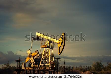 Oil pump jacks at sunset sky background. - stock photo