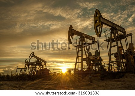 Oil pump jacks at sunset sky background. Toned. - stock photo