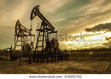 Oil pump jacks at sunset sky background. Toned. - stock photo