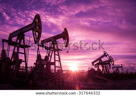 Oil pump jacks at sunset sky background. Toned.