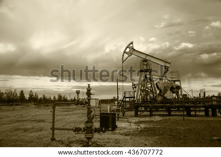 Oil pump jacks group and wellhead with valve armature during sunset on the oilfield. Oil and gas concept. Dramatic cloudy sky background. Toned sepia.