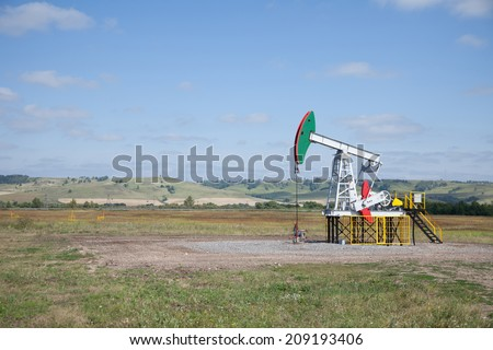 Oil pump. Oil industry equipment. Work of oil pump jack on a oil field. - stock photo