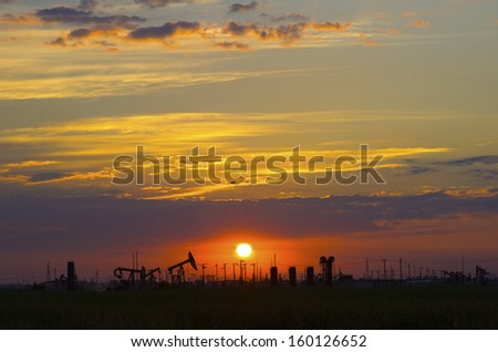 Oil pump oil rig in the sunset background for design - stock photo