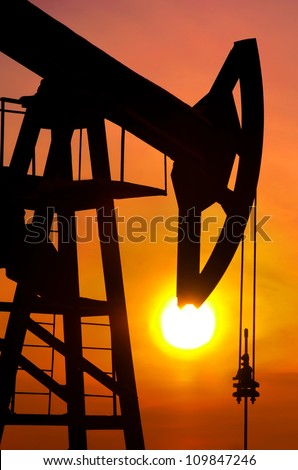 Oil pump rocker close to sunrise background - stock photo