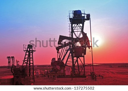Oil pump sunset silhouette - stock photo