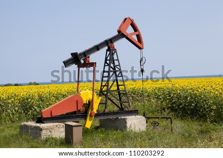 oil pump with sunflowers field on the background - stock photo