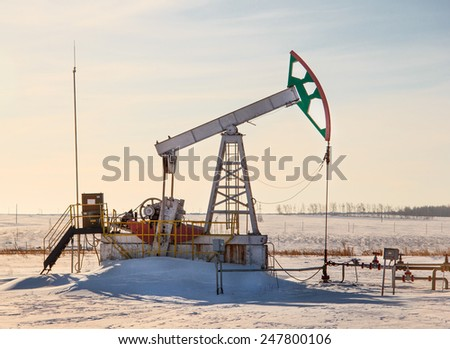 oil pump works on winter forest background - stock photo
