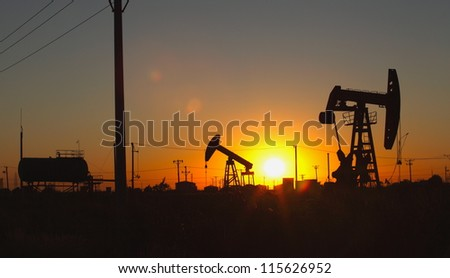 Oil pumping Unit at sunset time - stock photo